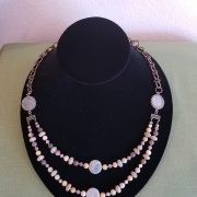 Doouble strand of beads flanked by two Roman coins